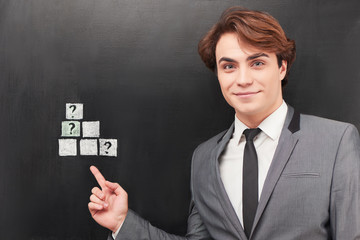 Businessman pointing at cubes painted on chalkboard