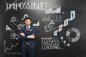 Smiling businessman and chalkboard with colorful graphs on it