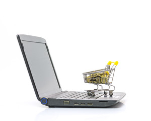 Shopping cart with full of gold coins over a laptop