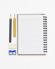 High angle shot of blank note book, pencil, sharpener