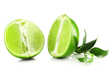 Juicy halves of lime with green leaves isolated on white