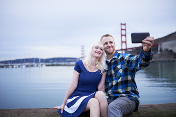 couple taking romantic selfie by golden gate bridge