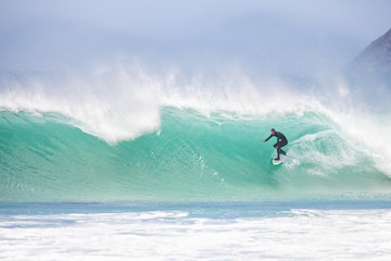 Surfer riding large turquoise wave
