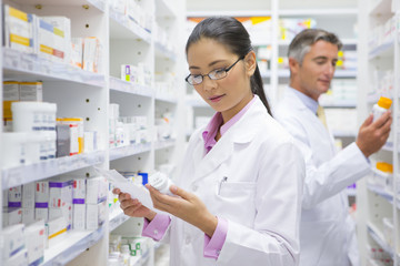 Pharmacists reading pack of medicine and prescription from pharmacy shelf