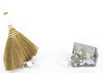 isolated broom and wastebasket full of waste newspaper