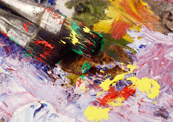 Art still life - two paintbrushes and dirty palette with colourf