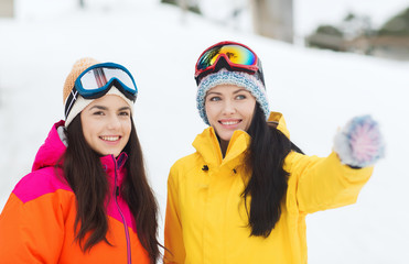 happy girl friends in ski goggles outdoors
