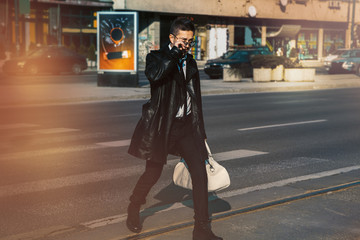 man in a leather coat and sunglasses crossing the road