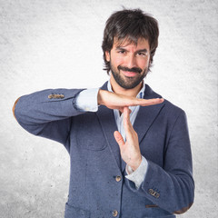 Happy man making time out gesture over white background