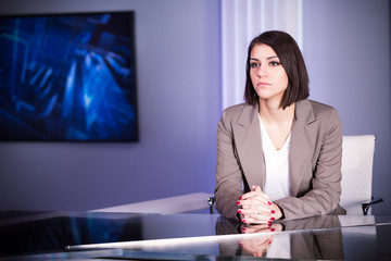 Beautiful television announcer at studio during live broadcast