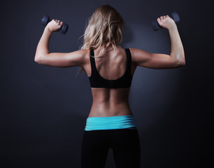 Sport back of atletic woman with dumbbells.