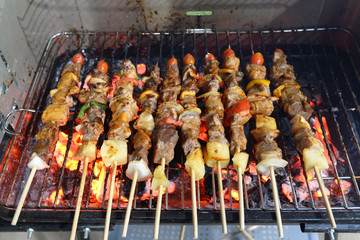 kebabs skewered with peppers over the coals of a barbecue