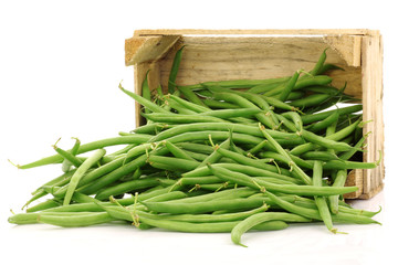 bunch of green beans in a wooden box on a white background