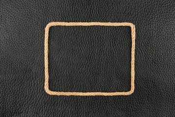Frame of rope, lies on a background of a black natural leather