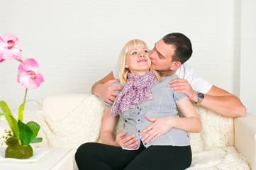 man kissing pregnant wife