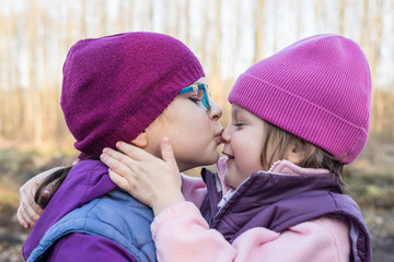 sister lovingly kissing her younger sister