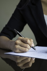 closeup of woman hand signing a contract
