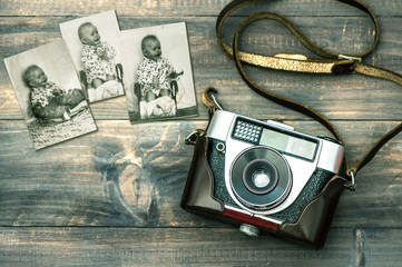 Vintage camera and old baby photos. Retro style toned picture