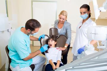 Kleines Mädchen mit ihrer Mutter beim Zahnarzt