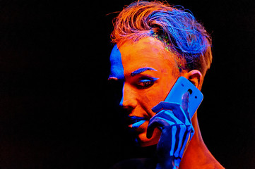 Man covered with fluorescent paint playing in the dark