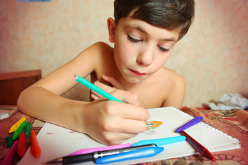 preteen handsome boy drawing with colored pencils and crayons