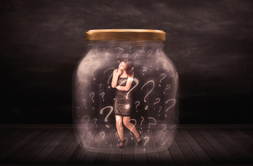 Businesswoman locked into a jar with question marks concept