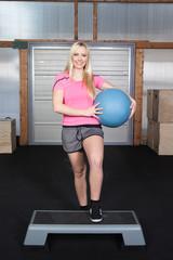 Woman aerobic training on a stepper with a medicine ball
