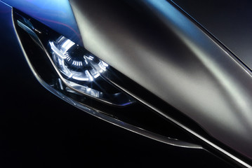 Predatory car headlight and hood of powerful sports grey car