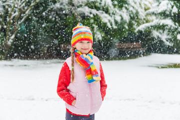 Winter portrait of a cute little girl under the snowfall