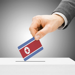 Voting concept - Male inserting flag into ballot box - North Kor