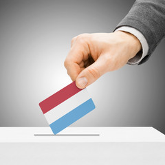 Voting concept - Male inserting flag into ballot box - Luxembour