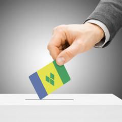 Voting concept - Male inserting flag into ballot box - Saint Vin