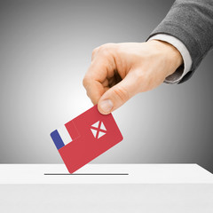 Voting concept - Male inserting flag into ballot box - Wallis an
