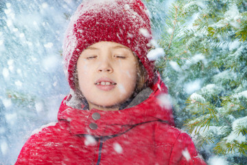 Portrait of boy with closed eyes and falling snow