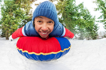 Close-up of excited boy on snow tube in winter