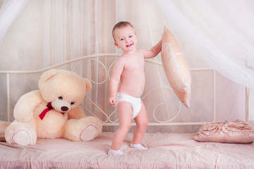 little boy playing with toys on the bed