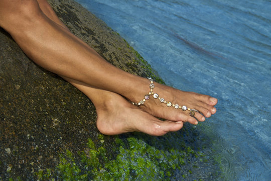 Female feet on wet stone with bracelet on ankle