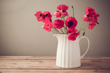 Poppy flower bouquet in white jug on wooden table