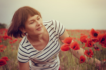 Attractive middle-aged woman has fun on a poppy field, summer ou