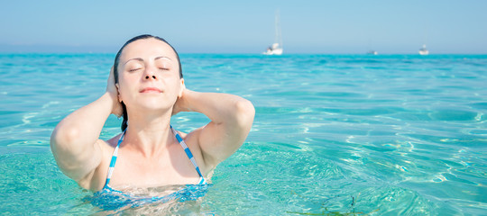 Young woman is relaxing in a heavenly sea Saleccia beach Corsica