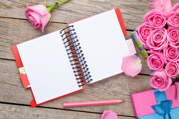 Blank notepad and gift box full of pink roses
