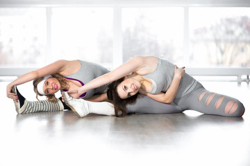 Sporty young females doing exercises for flexibility