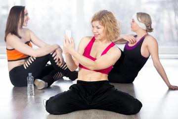 Sporty woman using smartphone on break in fitness class