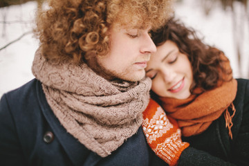 Young calm couple sitting in winter forest together