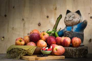 Still life of cat doll and group of organic apples