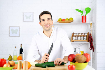 Man at table with different products in kitchen