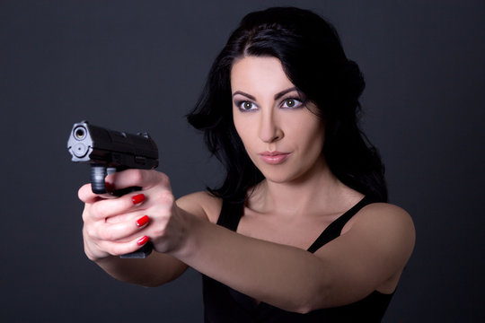 young sexy woman aiming with gun over grey