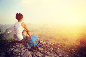 woman hiker enjoy the view at sunset mountain peak cliff Wall mural