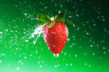 Strawberry on a green background with drops of water