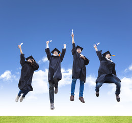 Happy young group of graduation students jumping together
